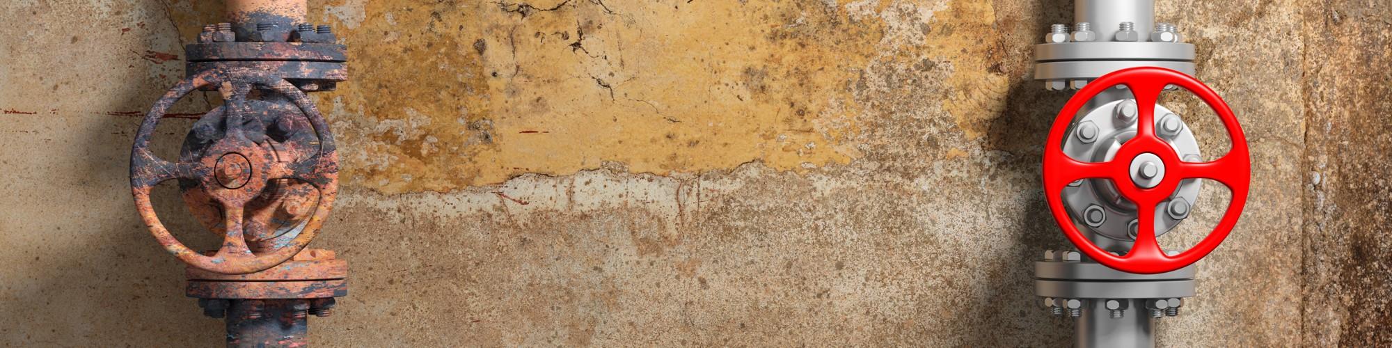 Bild: Alter, verrosteter und neuer Wasserschieber an fleckiger Wand